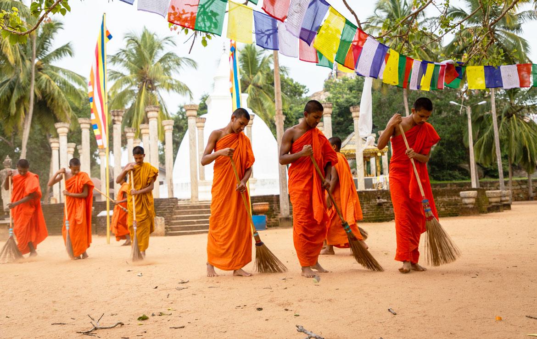 vegende monniken in oranje kleding bij tempel in sri lanka